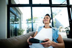 Pregnant woman listening to music on sofa Royalty Free Stock Photography