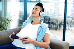 Pregnant woman listening to music on sofa Stock Photo