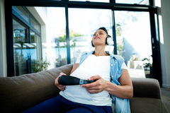 Pregnant woman listening to music on sofa Stock Images