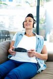 Pregnant woman listening to music on sofa Royalty Free Stock Images
