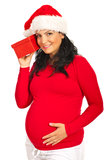 Pregnant woman listening to Xmas gift Royalty Free Stock Image