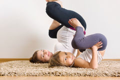 Pregnant woman and little daughter yoga exercising Stock Photo