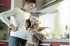 Pregnant woman and little girl cooking in the kitchen stock photography