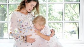 Pregnant woman with little son on window sill. Little boy kissing pregnant mother in belly sitting together on window sill in sunlight stock image