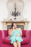 Pregnant woman in living room talking on telephone Stock Images