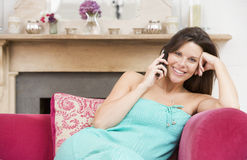 Pregnant woman in living room talking on telephone Royalty Free Stock Image