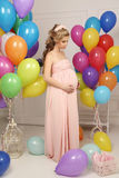 Pregnant woman with long blond hair in elegant dress, with a lot of colorful air balloons Royalty Free Stock Photos