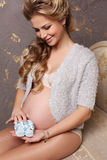 Pregnant woman with long blond hair sitting on divan, holding small baby shoes Royalty Free Stock Images