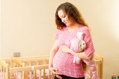 Pregnant woman with long hair with toy Teddy bear in a crib at home Stock Image