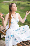 Pregnant woman with long hair in a yoga pose Royalty Free Stock Photography