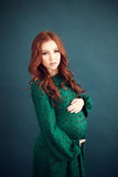 Pregnant woman in long lace green dress Stock Images
