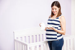 Pregnant woman looking at baby clothes Royalty Free Stock Photos