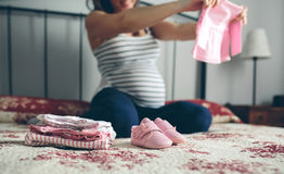 Pregnant woman looking baby girl cardigan Royalty Free Stock Photos