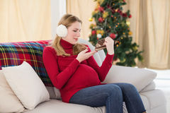 Pregnant woman looking at baby shoes sitting on sofa Royalty Free Stock Image