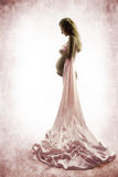 Pregnant woman looking at belly. Silk dress, cloth.  Grunge background. Vintage style Royalty Free Stock Photo