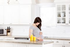 Pregnant Woman Looking at Belly Stock Photography