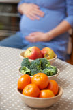 Pregnant Woman Looking At Bowls Of Healthy Fruit And Vegetables Stock Photo