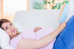 Pregnant woman looking at camera and reading a book Royalty Free Stock Images