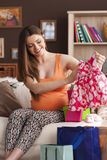 Pregnant woman looking clothes for baby Royalty Free Stock Images
