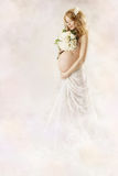 Pregnant woman looking at flowers in white dress. Stock Images