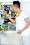 Pregnant woman looking in fridge. Pregnant looking for food in refrigerator Royalty Free Stock Images