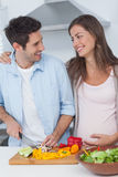 Pregnant woman looking at husband chopping vegetables Royalty Free Stock Photo