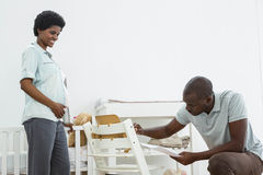 Pregnant woman looking at man fixing a baby chair Stock Photos