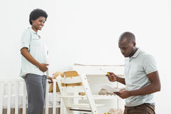 Pregnant woman looking at man reading a list while fixing a baby chair Stock Photos