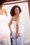 Pregnant woman looking in mirror Stock Photo