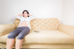 Pregnant woman looking seriously sitting on couch. Royalty Free Stock Photo