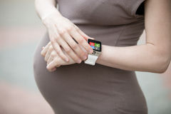 Pregnant woman looking at smartwatch. Close-up Royalty Free Stock Images