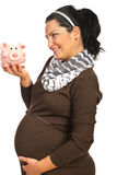 Pregnant woman looking to piggybank Royalty Free Stock Images