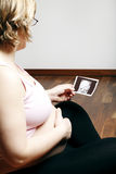 Pregnant woman looking at ultrasound image. Pregnant woman seated in a chair looking at an ultrasound image of her unborn foetus royalty free stock photography