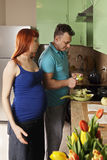 Pregnant woman looks at guy peeling apple royalty free stock photo