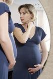 Pregnant Woman Looks in Mirror Stock Images