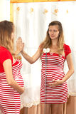 The pregnant woman looks in a mirror Stock Photography