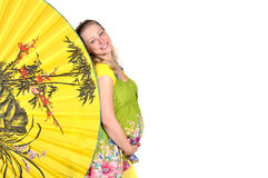 Pregnant woman looks out a yellow fan Royalty Free Stock Photos