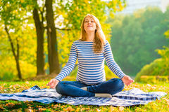 Pregnant woman in a lotus position Stock Photography