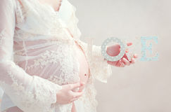 Pregnant woman lovingly embraces the stomach Royalty Free Stock Images