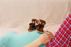Pregnant woman lying with baby shoes on her stomach Royalty Free Stock Images