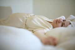 Pregnant woman lying in bed. Pregnant woman in bathrobe and towel lying in soft bed Royalty Free Stock Image