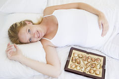 Pregnant woman lying in bed with chocolates Royalty Free Stock Images