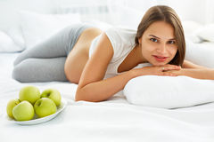 Pregnant Woman lying on the Bed with fresh Apples. Healthy Food Royalty Free Stock Photo