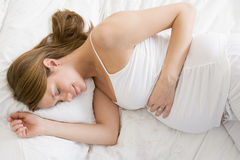 Pregnant woman lying in bed sleeping Stock Photo