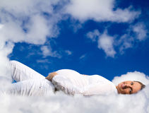 Pregnant woman lying on clouds. Beautiful Pregnant woman lying on floating white clouds in the blue sky Stock Photo