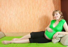 Pregnant woman lying down  at home Stock Photography