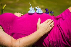 Pregnant woman lying on a grass with baby shoes on her belly Stock Photography