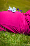 Pregnant woman lying on a grass with baby shoes on her belly Stock Photos