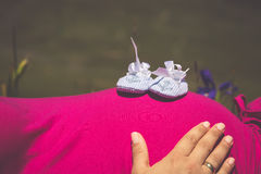 Pregnant woman lying on a grass with baby shoes on her belly Stock Image
