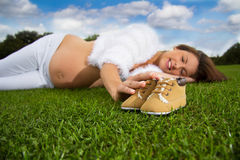 Pregnant woman lying on the grass. Beautiful pregnant woman lying on the grass under a blue sky touching a baby shoes Royalty Free Stock Photos